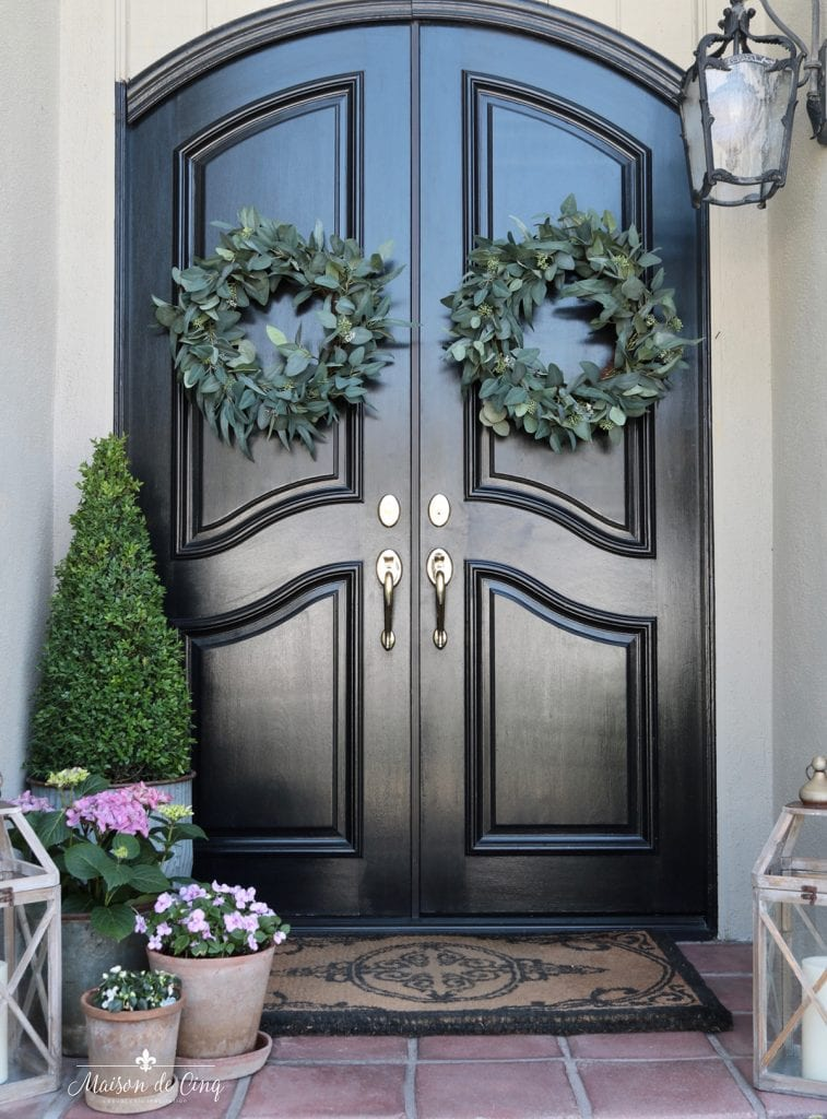 front doors with wreaths and flowers create a beautiful spring front porch