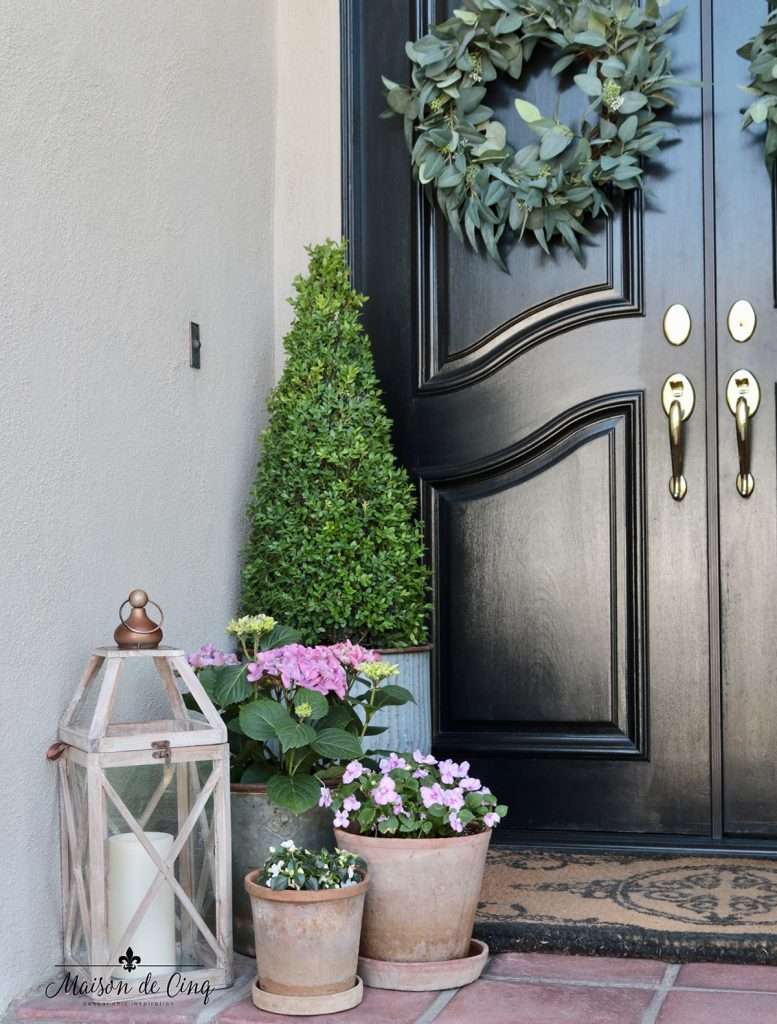 spring front porch decorating ideas with lantern boxwood topiary and pink flowers