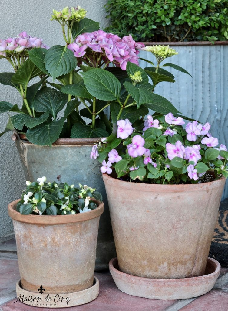 pots of impatiens and hydrangeas in pink and white pretty spring front porch decor
