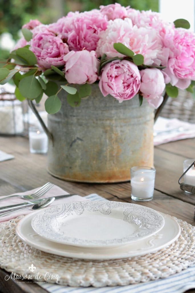 spring table decor peonies with blue and white placemats candles and seagrass chargers