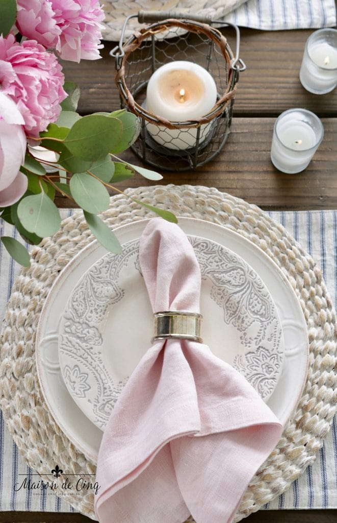 gorgeous spring table decor idea pink napkin blue and white plates seagrass charger and candles