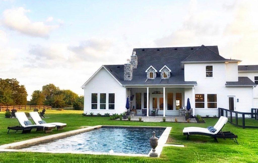 modern Texas farmhouse with reflecting pool and grass surround beautiful backyard