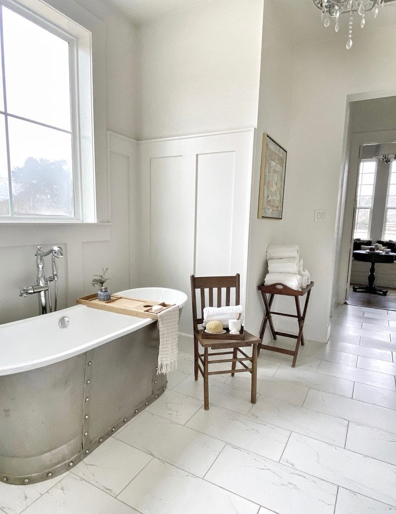 white modern farmhouse bathroom with gorgeous zinc tub and marble floors