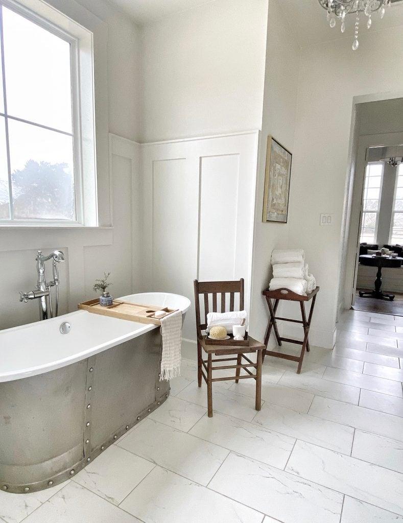 white modern farmhouse bathroom with gorgeous zinc tub and marble floors