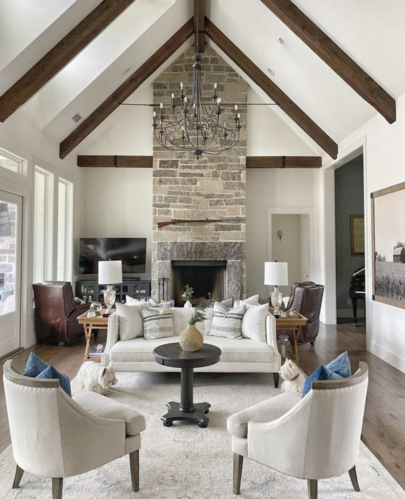 dramatic stone fireplace in modern farmhouse living room vaulted ceilings with beams