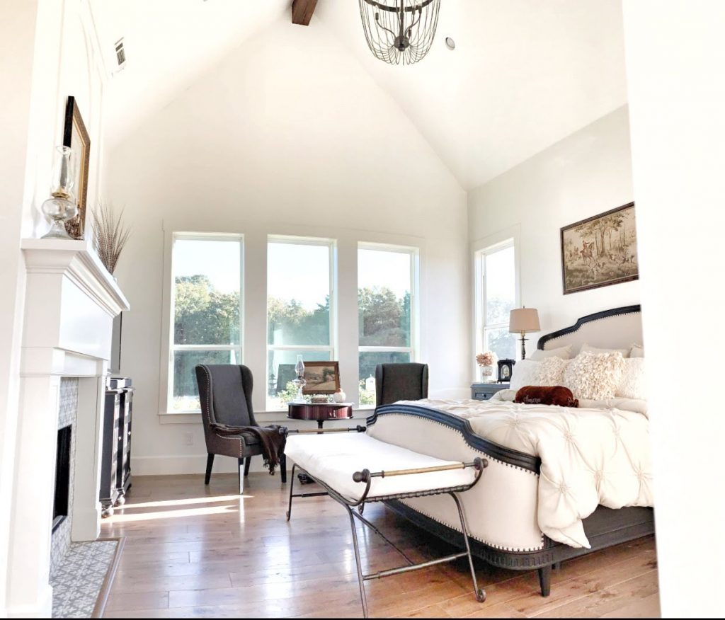 farmhouse style master bedroom with windows and fireplace