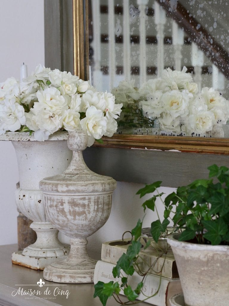 ivy in pot with urn and roses on console table French country style