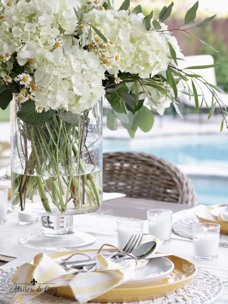 gorgeous cheerful summer table setting with white hydrangeas and chamomile centerpiece yellow plates