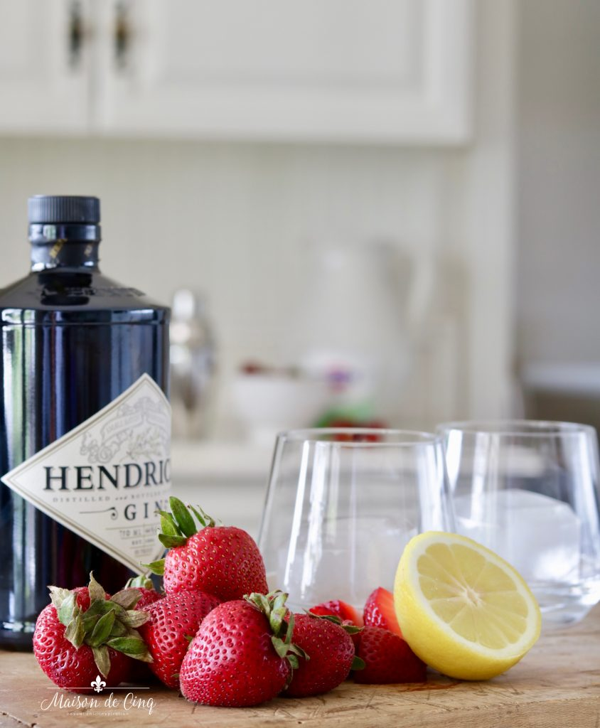 strawberries, gin, ice and lemon ingredients in summer cocktail