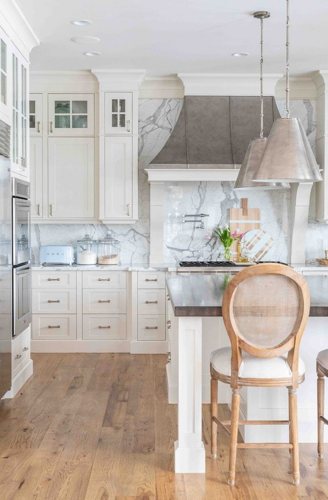 stunning white kitchen with marble backsplash and zinc range hood in French style home