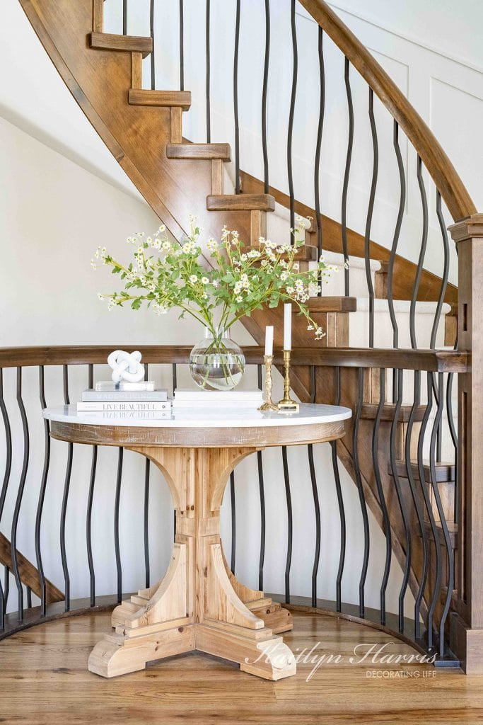 entryway with beautiful staircase railing and round table