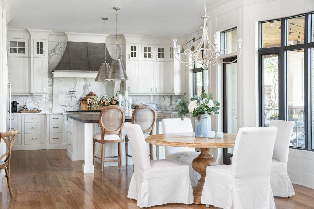 stunning French style home kitchen and dining area white marble countertops wood dining table and parsons chairs