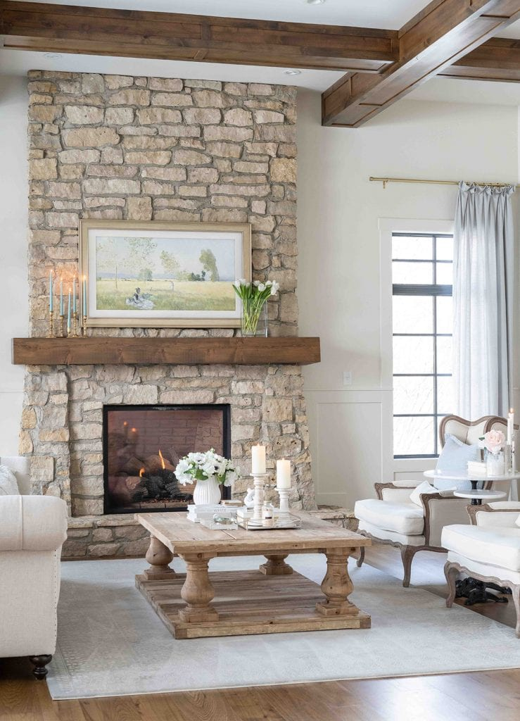 French style home gorgeous living room with stone fireplace and wood ceiling beams