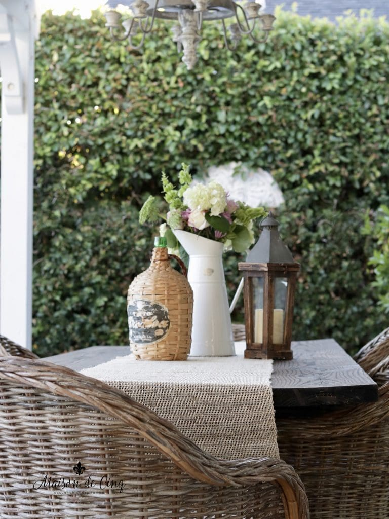 flowers and wicker demijohn on outdoor table summer decorating