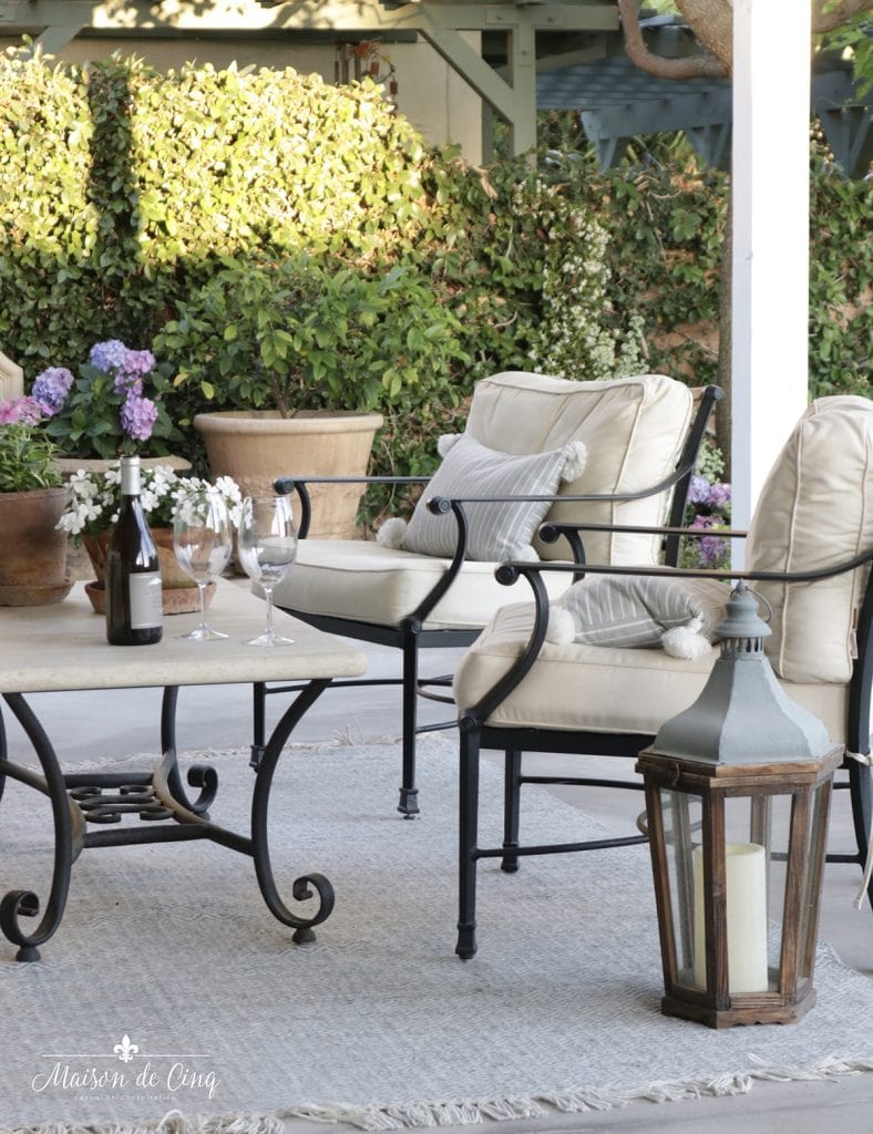 outdoor furniture lanterns and flowering planters on patio
