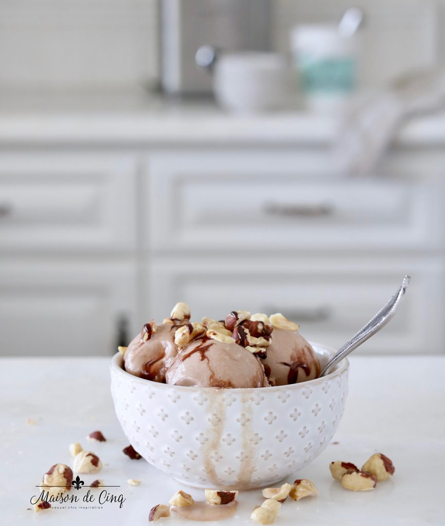 bowl of gelato on counter with chocolate syrup and hazelnuts on top