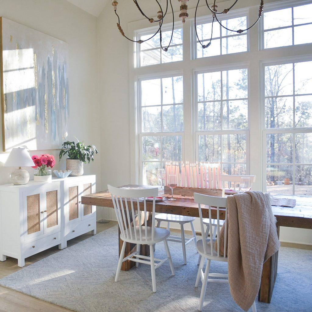 coastal farmhouse dining room with modern art and pretty rug
