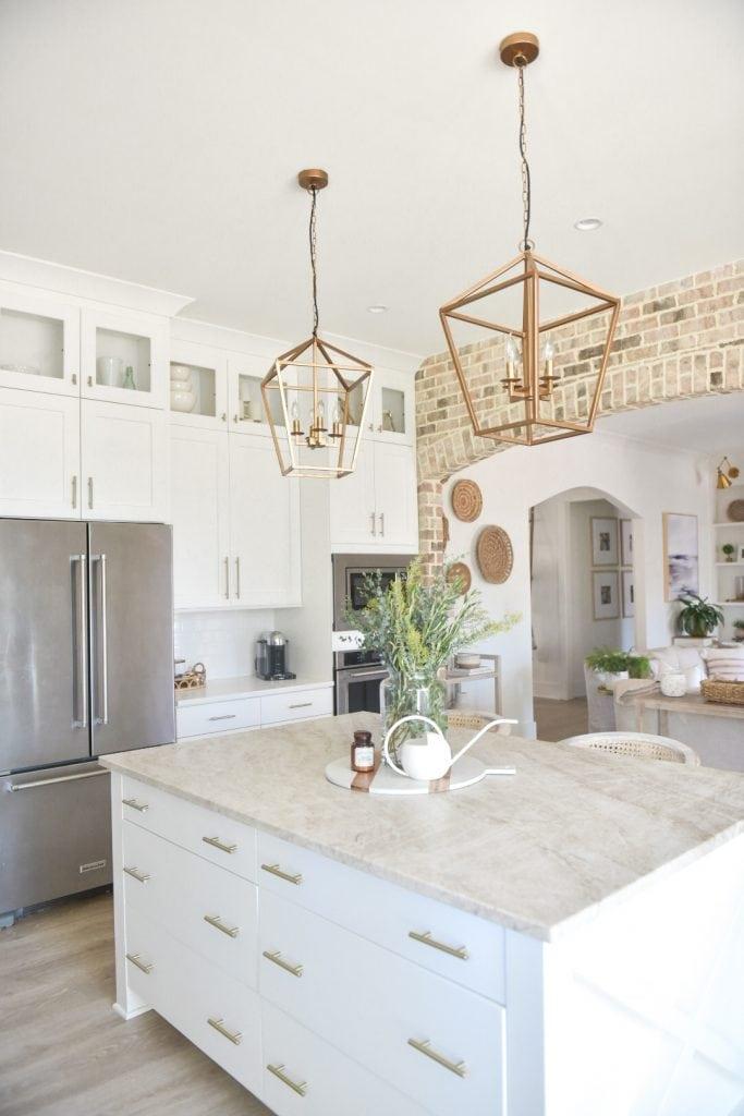 gorgeous coastal farmhouse style kitchen with brass pendants