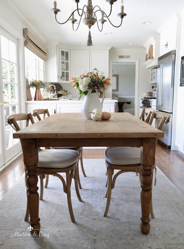 farmhouse table with fall flowers and pumpkins fall decor in white kitchen