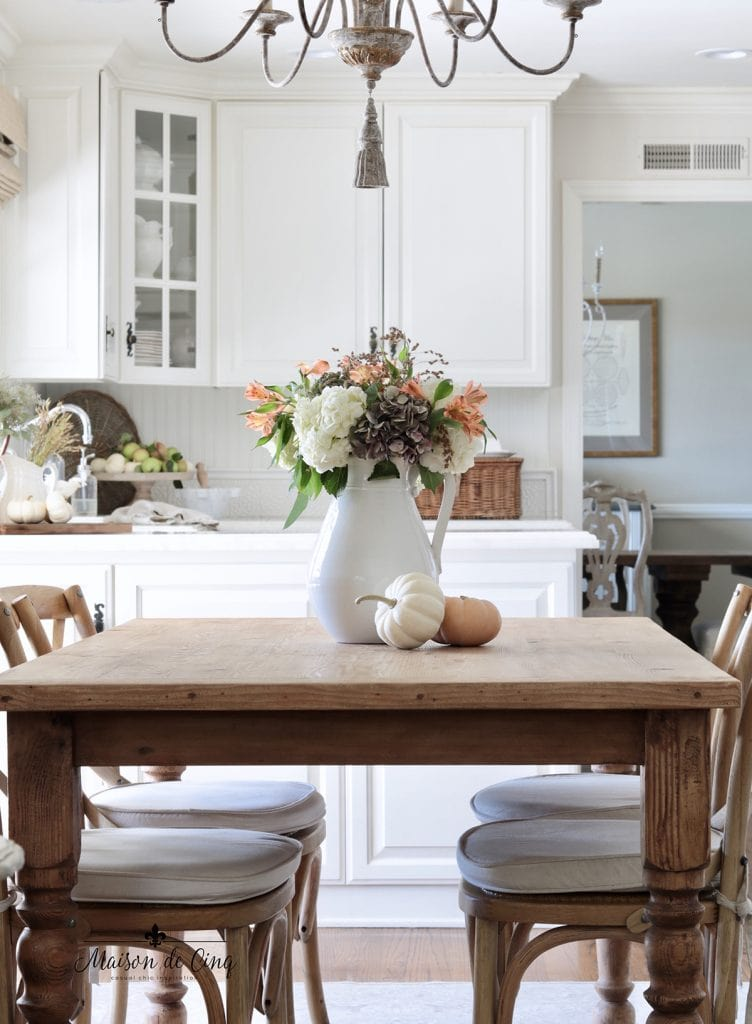 pretty fall flowers with pumpkins on farmhouse table white kitchen fall decorating