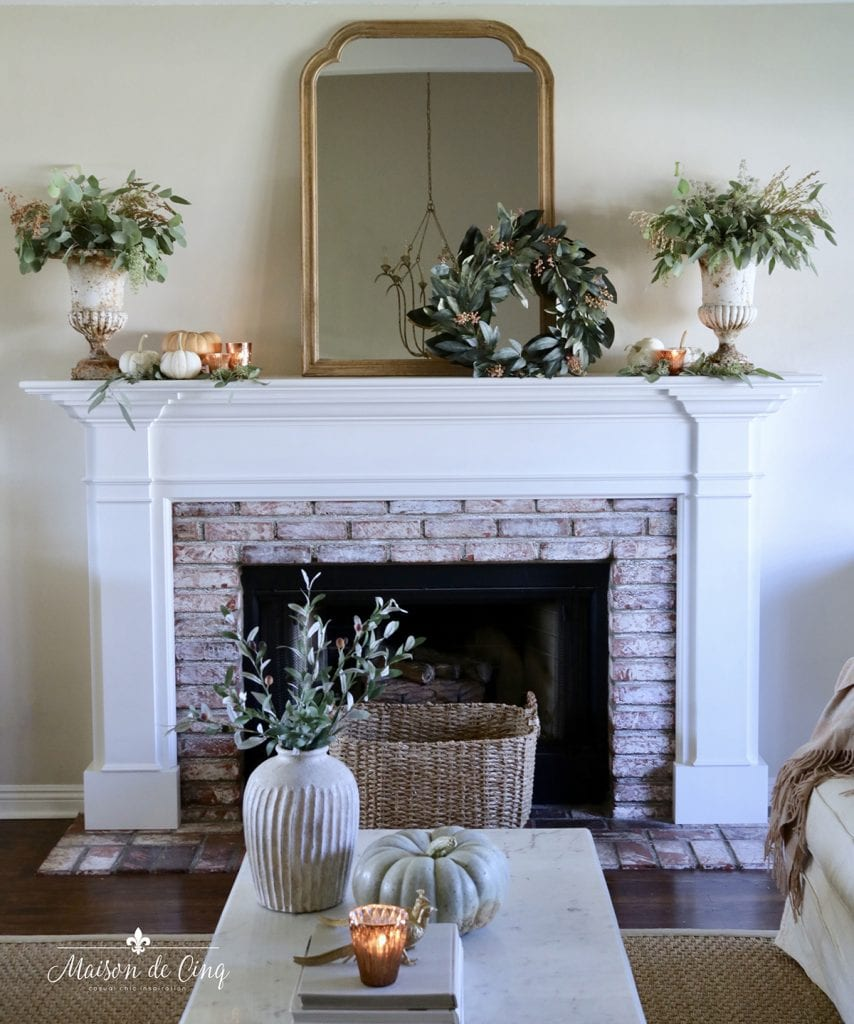 gorgeous French farmhouse living room with subtle fall mantel decor wreath pumpkins and greenery