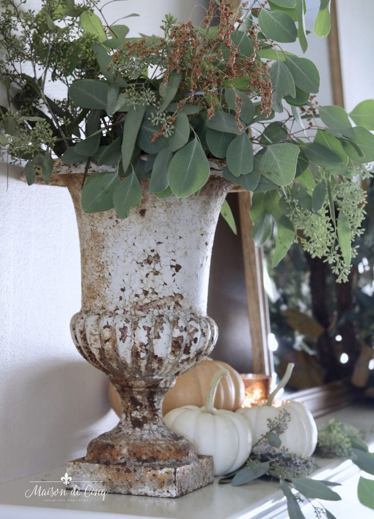 French cast iron urn chippy vintage style with fall greenery and grasses