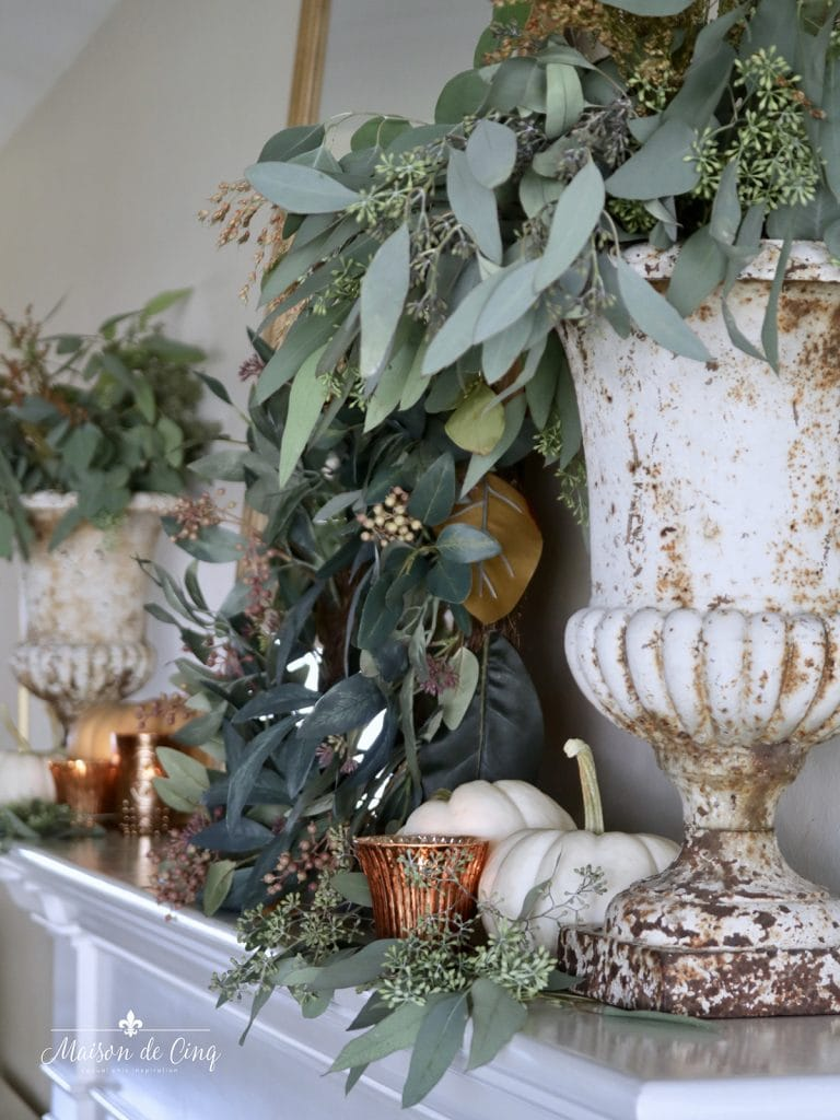gorgeous simple fall mantel decor eucalyptus in French urns and copper votives autumn decor