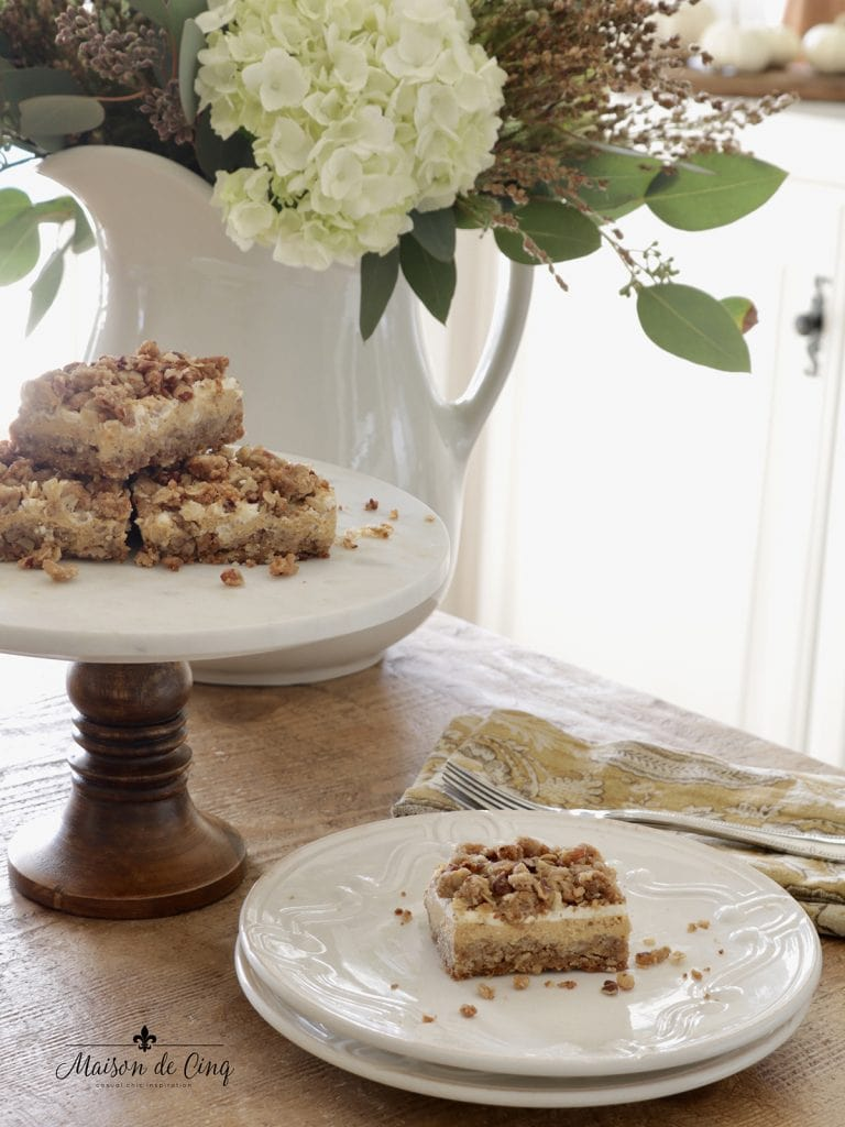 pumpkin cheesecake crumble bars with flowers and plates serving fall dessert
