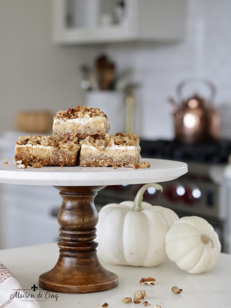 pumpkin cheesecake crumble bars on cake stand with white pumpkins in white kitchen
