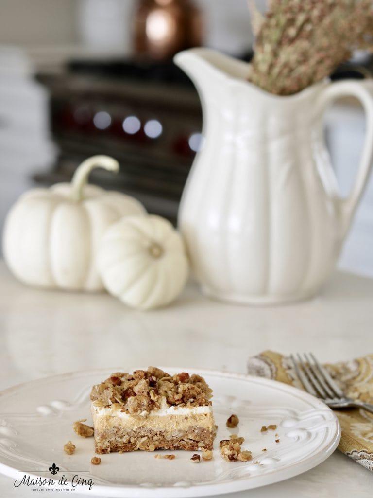 pumpkin cheesecake bar on plate near pumpkins fall autumn dessert