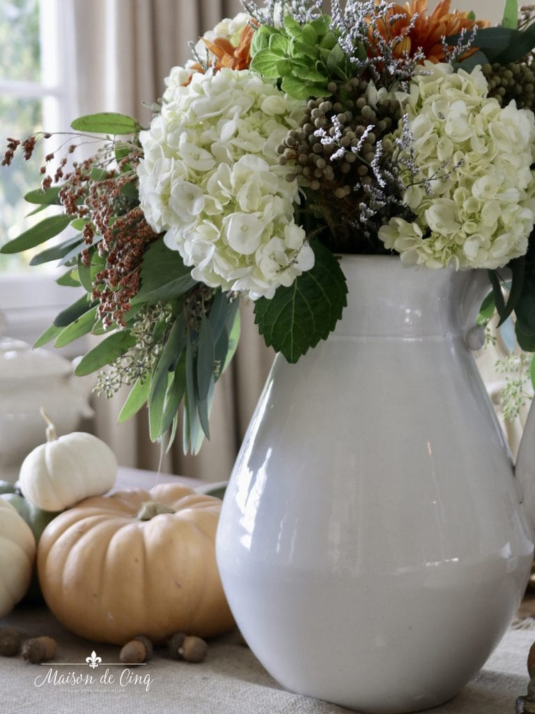 gorgeous fall florals in white pitcher with pumpkins and acorns autumn centerpiece ideas