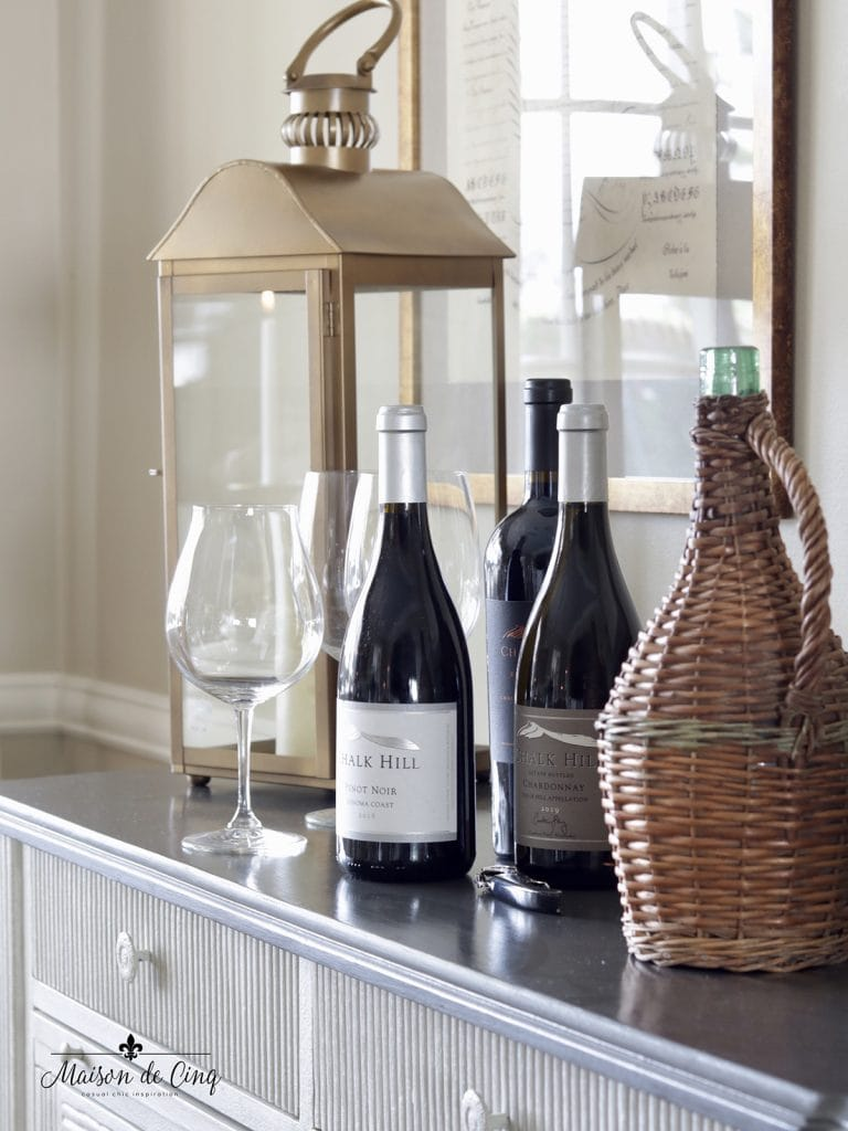 extra wine for party with brass lanterns and wicker wine bottles