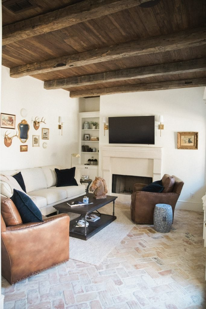 french farmhouse style den with wood planked ceiling and brick floors