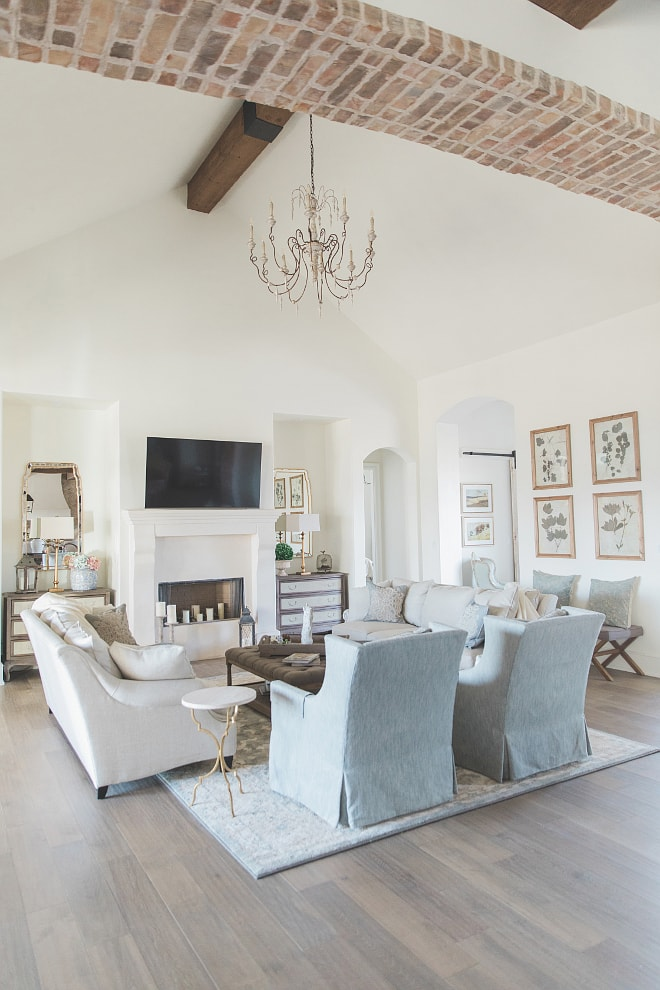 French farmhouse style home living room with brick archway blue linen chairs and french chandelier