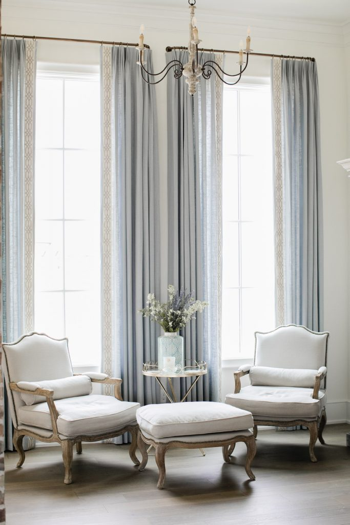 beautiful blue draperies in master bedroom sitting area with french chairs and chandelier