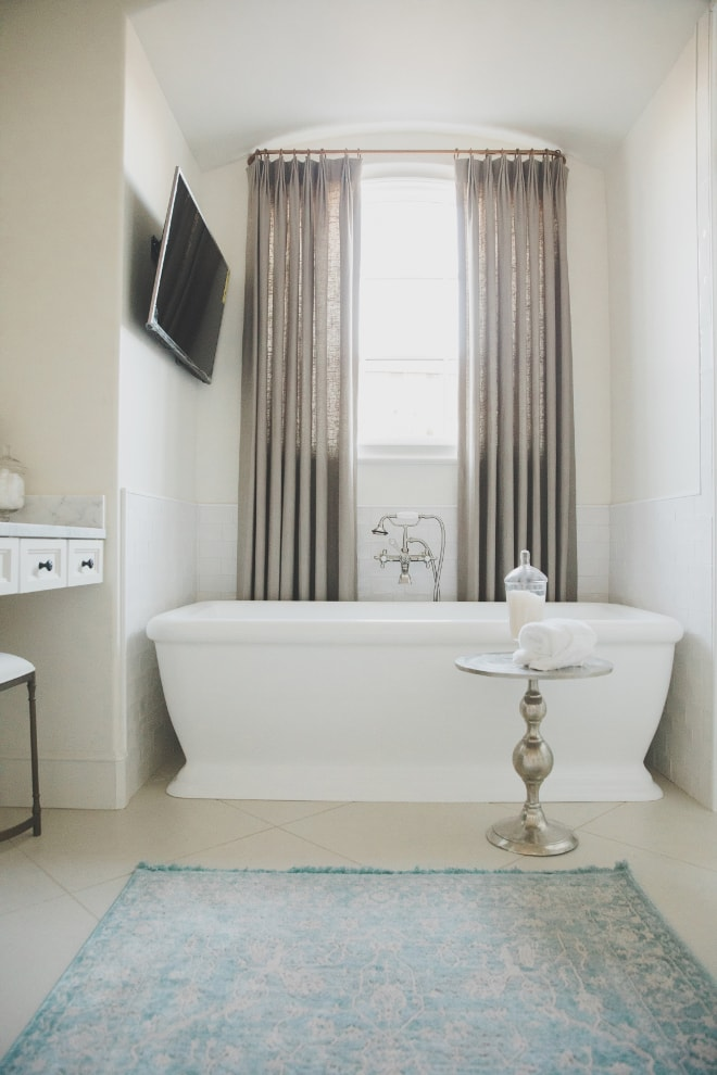 French country master bathroom with free standing tub and blue rug