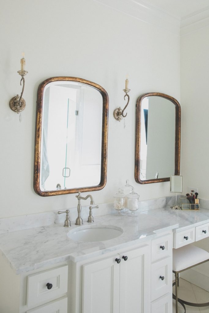 French farmhouse country bathroom with gold mirrors marble counters and sconces
