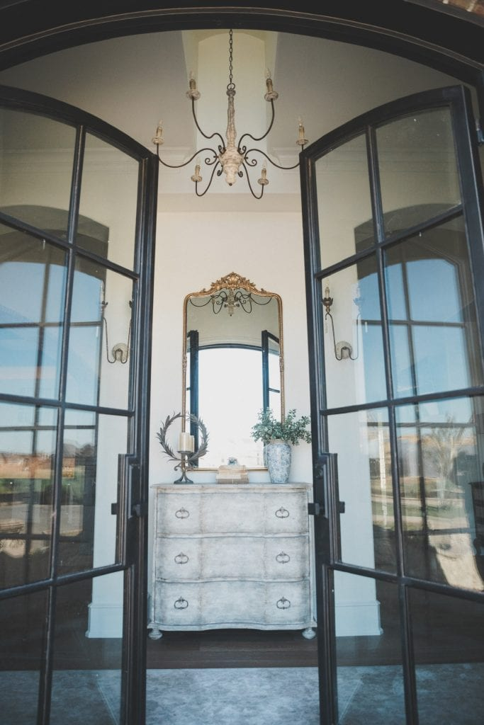 gorgeous glass front doors to french inspired entry way with chandelier