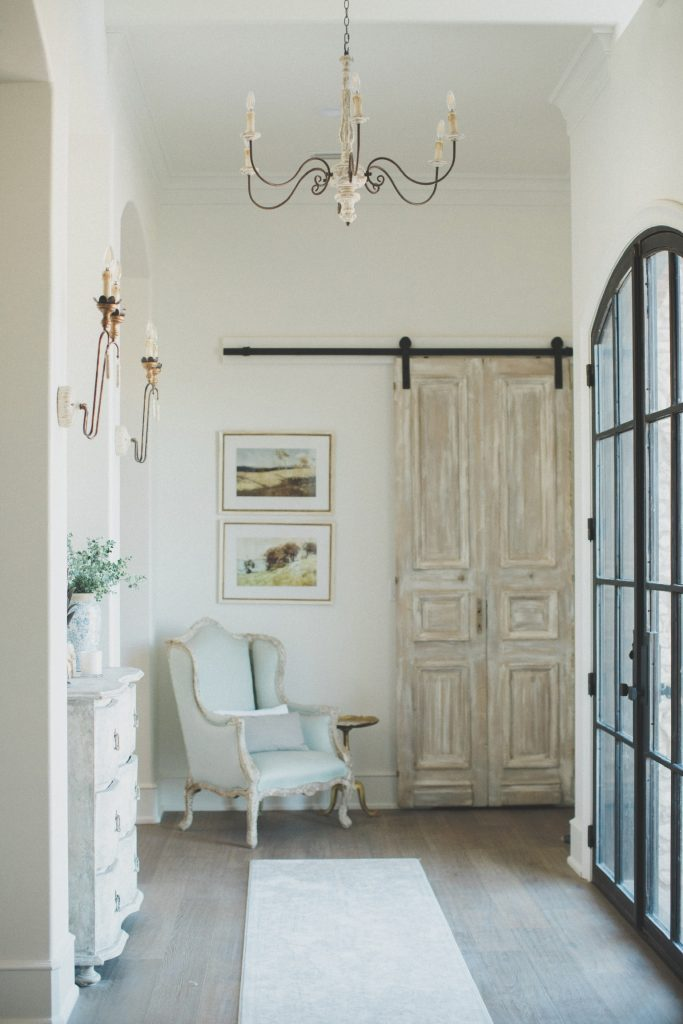 french farmhouse style entry way with barn door and gorgeous chandelier