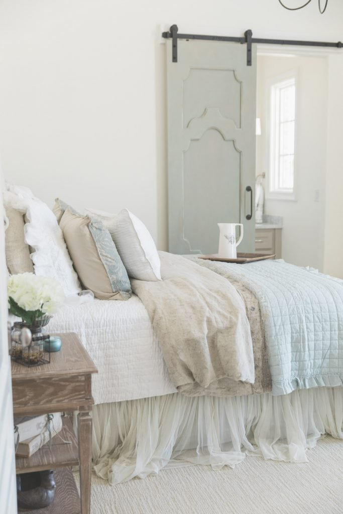 French farmhouse inspired bedroom with spa blue bedding and barn door