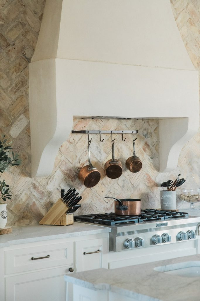 rustic stone range hood and brick backsplash french country kitchen with copper pots