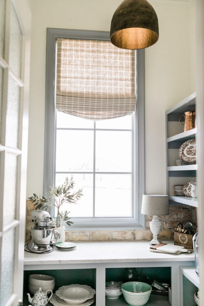 french farmhouse inspired pantry with roman shade and brick backsplash