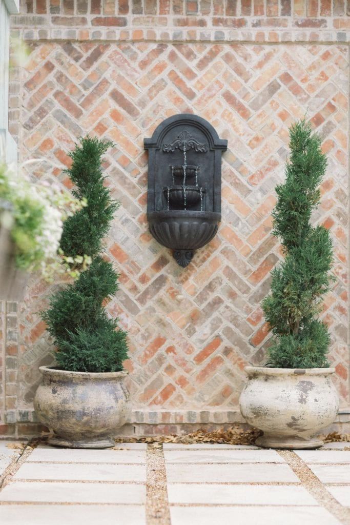 potted topiaries in French pots with wall fountain and brick wall French farmhouse country style outdoor space