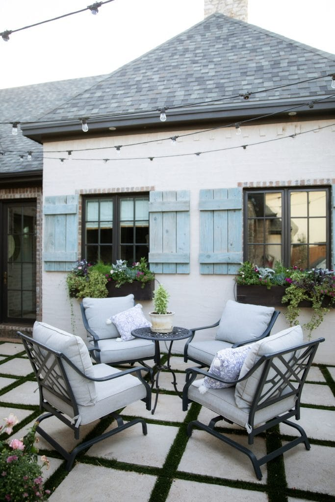 outdoor backyard sitting area with blue shutters on windows French inspired charm
